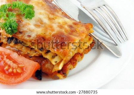 Lasagna and tomatoes with utensils on a white plate. - stock photo