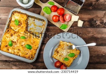 Lasagna bolognese, beef, parmesan, Italian classic, simple serving, wood board - stock photo