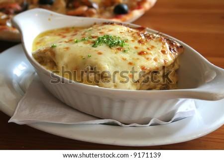 Lasagna in baking dish Italian cuisine melted cheese - stock photo