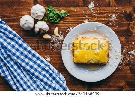 Lasagna on a white plate with wooden background. Sprinkle with parmesan cheese. Fresh garlic and parsley. Texture of dark mahogany - stock photo