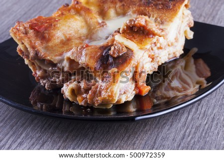 Lasagna over black reflecting plate, horizontal image