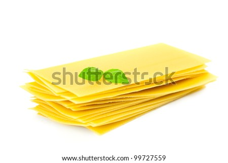 Lasagna pasta with basil herb leaf sprig isolated over white background - stock photo