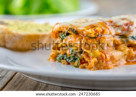 Lasagna with garlic bread and salad - stock photo