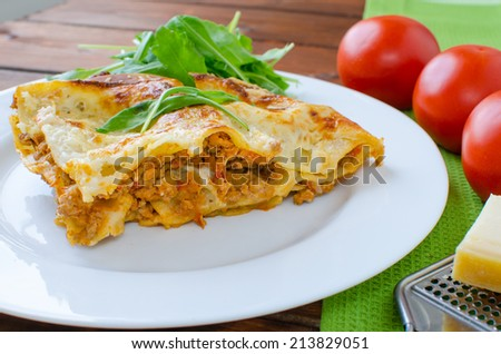 Lasagne bolognese on white plate, tomato and cheese grater