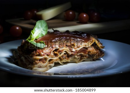 Lasagne with tomato and vegetables on dark background