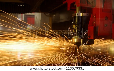 Laser cutting of metal sheet with sparks - stock photo