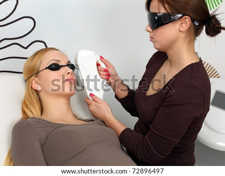 Laser hair removal in professional studio. Pro at work with her client. - stock photo
