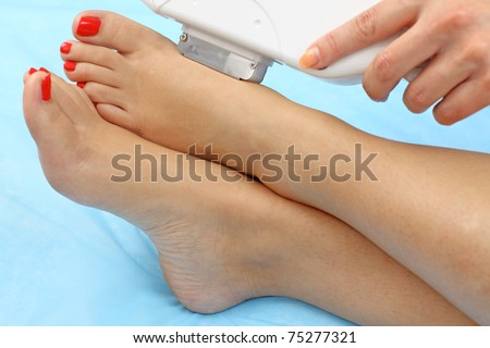 Laser hair removal on lady's legs. Intentional shallow depth of field. - stock photo