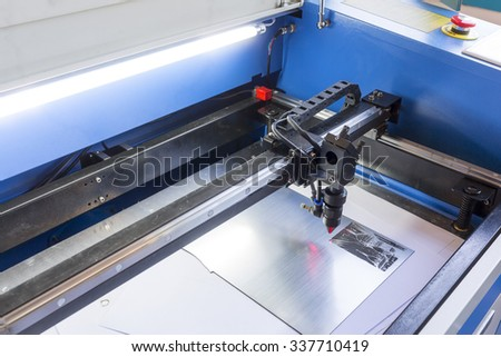 Laser machine is cutting an image on a flat sheet ot steel in a university laboratory. - stock photo