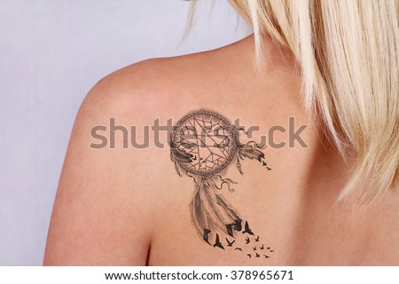 Laser tattoo removal concept. Beautiful young woman with tattoo on her back - stock photo