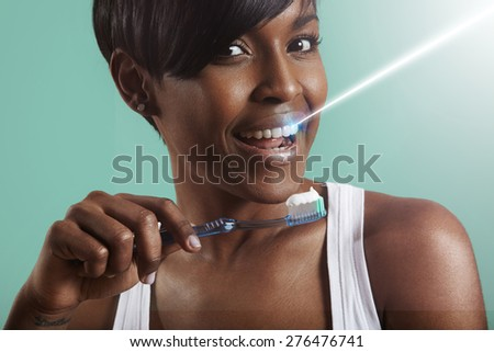 laser whitening concept, black woman cleaning her teeth ray of laser - stock photo