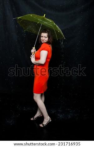 lass with an umbrella stands under rain - stock photo