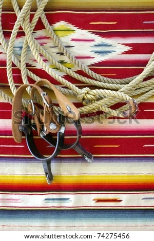 Lasso and spurs on colorful woven blanket - stock photo