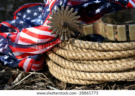 Lasso, spur and patriotic fabric on hay outside on a sunny day - stock photo