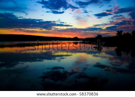 last bright sunrays above the lake late at cloudy evening - stock photo