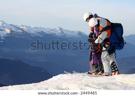 Last check of equipment before the paraskiers leave the mountain - stock photo