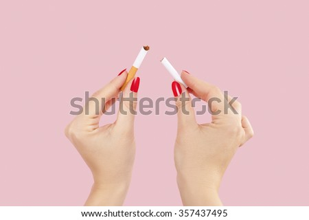 Last cigarette. Female hands with red fingernails breaking the last cigarette isolated on pink background. Quit smoking new year resolution. - stock photo