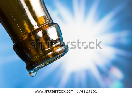 Last drop of an empty beer bottle with the sun in the background - stock photo