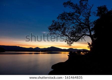 Last rays of sun over lake Loch Lomond, Scotland - stock photo