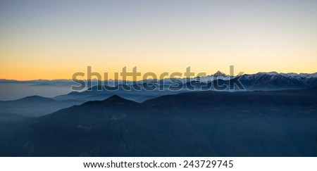 Last sunlight on the alpine arc with the majestic peak of M. Viso (3841 m) arising from the misty valley below. Panoramic frame, high contrast. Aerial view on the Susa Valley, Torino Province, Italy. - stock photo