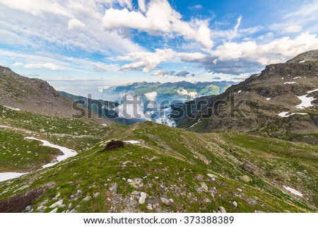 Last warm sunlight on Susa Valley with glowing mountain peaks and lush green meadows. Wide angle view from above with rocky extreme terrain in the foreground. - stock photo