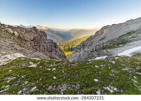 Last warm sunlight on Susa Valley with glowing mountain peaks and lush green woods. Wide angle from above view with rocks and flowering meadow in the foreground. - stock photo
