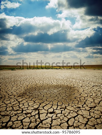 last wet spot in cracked earth under dramatic sky - stock photo