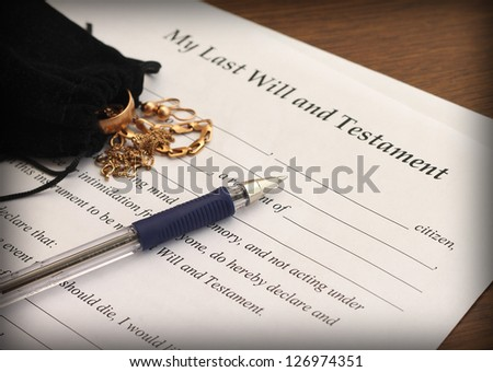 Last Will and Testament form with gold jewelry, close-up - stock photo