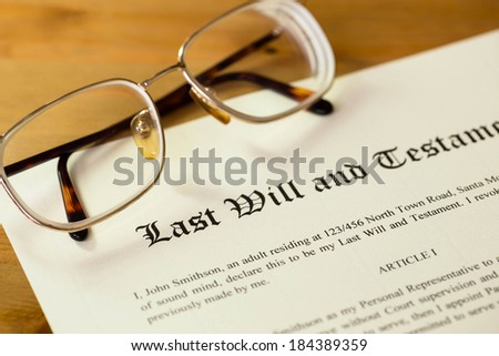 Last will and testament on cream color paper with glasses - stock photo