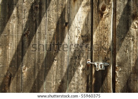 Latched wooden gate with diagonal shadows. - stock photo