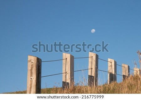 late afternoon moon rising against a blue sky with fence line  - stock photo