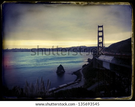 Late afternoon on a cloudy day above the San-Fransisco bay and Golden Gate bridge. Image stylized with vintage instant film aesthetics. - stock photo