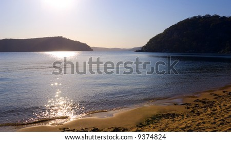 late afternoon sunlight dazzling reflections on coastal lake landscape with surrounding bushy hills and mountains. beautiful clear blue sky - stock photo