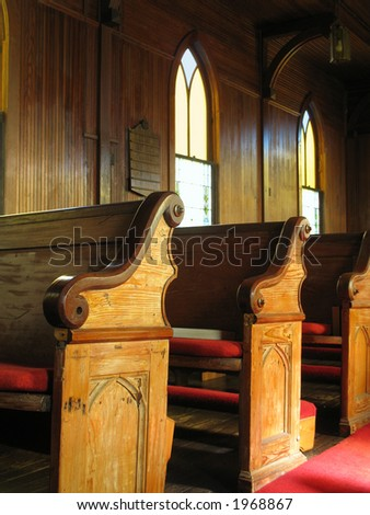 late afternoon sunlight falls across old cypress pews in a small town American church buillt in the early 1830s - stock photo