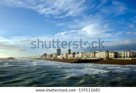 Late afternoon sunshine on Brighton Beach and the remains of the West Pier. - stock photo