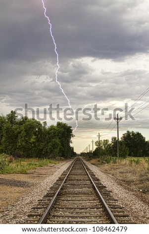 Late afternoon thunderstorms came rolling in and caught this lightning bolt striking next to the railroad track. - stock photo