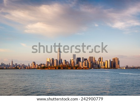 Late afternoon view of New York's majestic skyscrapers and Downtown Manhattan. Warm, glowing light flooding Lower Manhattan scenery, including the Financial District, Battery Park and Ellis Island. - stock photo