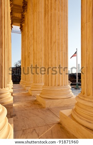 Late afternoon winter sun illuminates front of supreme court in Washington in winter with view of US flag - stock photo