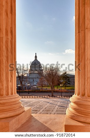 Late afternoon winter sun illuminates front of supreme court in Washington in winter with view of Capitol - stock photo