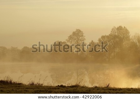 Late autumn trees on the shore of the lake at sunrise with the mist floating over the water. - stock photo