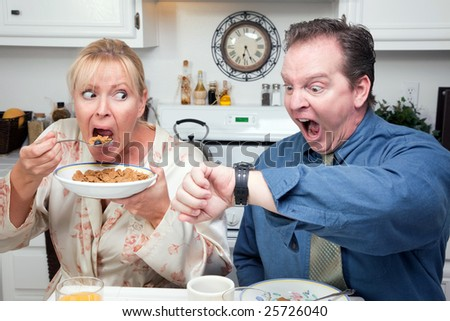 Late for Work Stressed Couple Checking Time in Kitchen. - stock photo