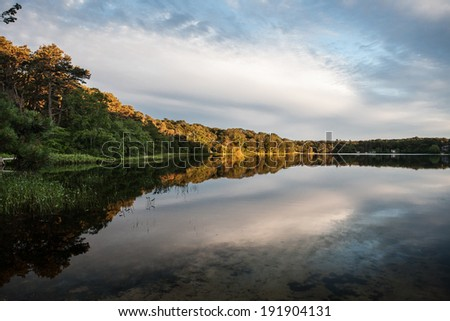 Late in the day clouds are reflected on the smooth surface of a freshwater lake on Cape Cod, Massachusetts. Ponds and lakes offer habitat for many native birds, fish, amphibians, and reptiles. - stock photo