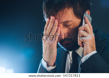 Late night business phone call with mobile, tired and exhausted businessman having conversation with his superior
