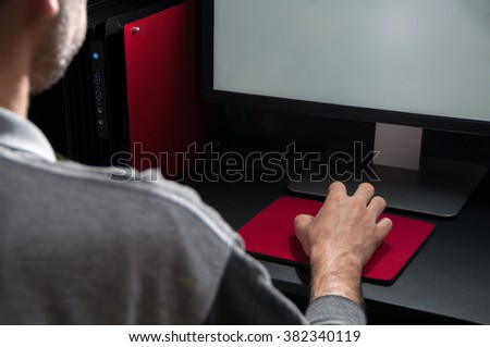 Late night internet addiction or working in the evening, man using desktop at a desk in the dark