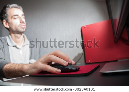 Late night internet addiction or working late man using desktop at a desk in the dark. Selective focus - stock photo