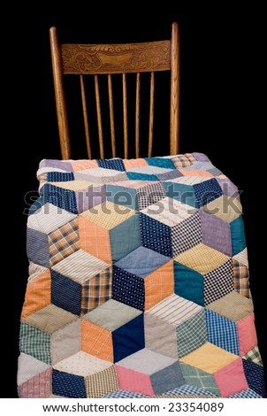 Late nineteenth century quilt and chair, black iso. - stock photo