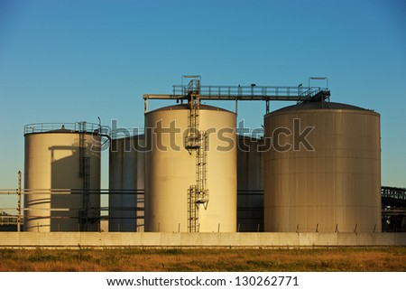 Late sunlight over an oil tanks - stock photo