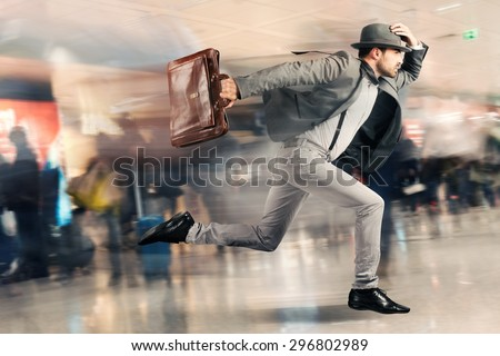 Late tourist man runs fast in airport - stock photo