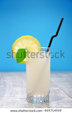 Lateral view of a glass of home made lemonade with a leaf of mint, a slice of lemon and a straw on a wooden table, on blue studio background