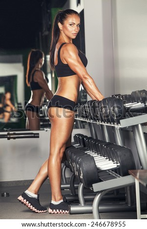laterally view of sexy young brunette woman resting in the gym and leaning on row of dumbbells. Fitness girl in gym in a black sport wear - stock photo